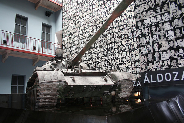 A Soviet tank and a wall full of photos of some of the victims that died in this building