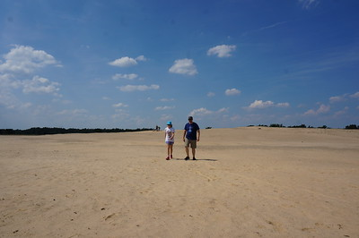 Ella and her father walking on a sand dune in the Hoge Veluwe National Park