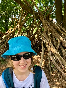 Ella outside of a stick fort in the Hoge Veluwe National Park