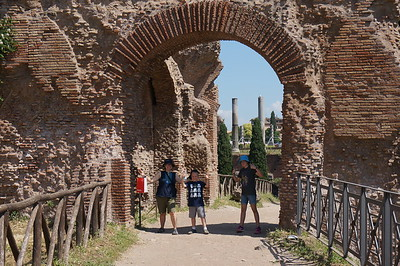 Karen and the kids walking through another old archway. Palatine Hill, Rome, Italy.