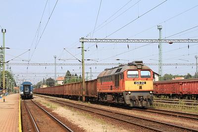 MÁV 628312 heads through Nagykanizsa with a lengthy rake of bogie wagons - 14/08/15.