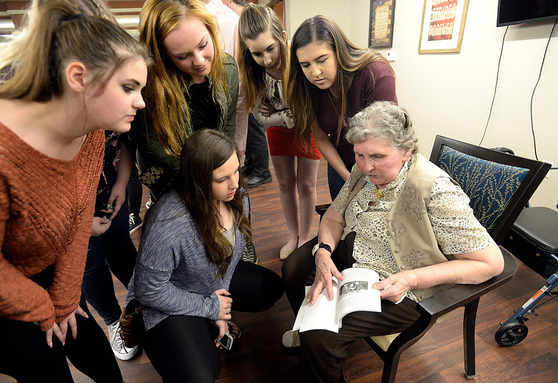 Eva Schumacher, a Good Samaritan Village resident, shows Mountain View High students a book about her family history Tuesday, April 16, 2018, after talking to them about her and her family's time in a Serbian war camp whne she was young. Clockwise from left are Summer Amdahl, 17, Jackie Smith, 16, Mary Hooper, 16, Kyara Corrall, 16, and Maddy Frink, 17.   (Photo by Jenny Sparks/Loveland Reporter-Herald)