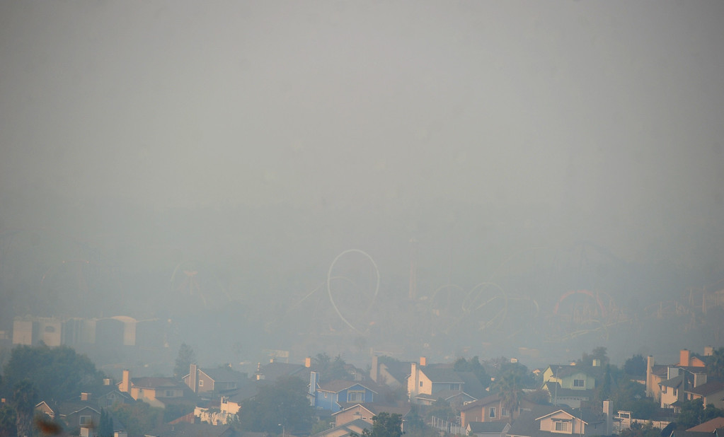. VALLEJO, CA- OCT. 10, The loops of roller coasters at Six Flags Discovery Kingdom can barely be seen through the smoke that blankets Vallejo from this view at Hunter\'s Hill. (Chris Riley/Vallejo Times-Herald)