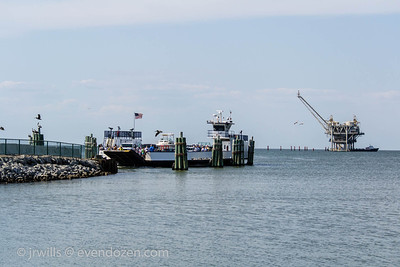 Pelicans, pilings, ferry, gas well and crew boat