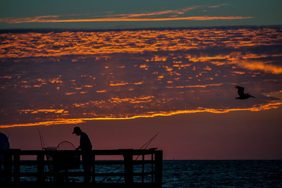 The silhouetted fisherman and the pelican in the foreground makes this shot more interesting.