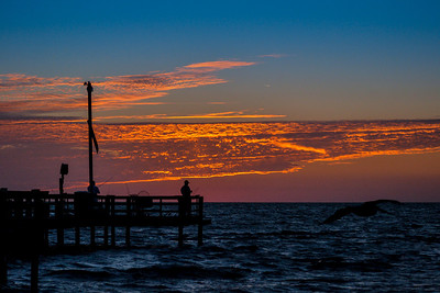 The silhouetted fishermen in the foreground make this shot more interesting. Did you notice the pelican?