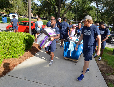 University of West Florida football players help students move their belongings into Argo Hall Friday, August 19, 2016 during Move in Day at the University of West Florida.