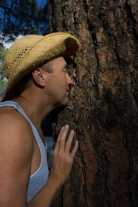 Videographer Jeffrey Lehmann hugging a tree at the South Rim of the Grand Canyon