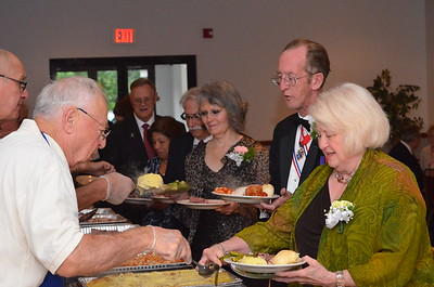 Head table dignitaries line up to fill their plates.