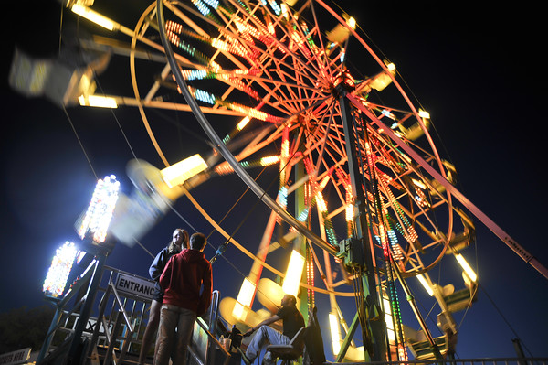 A young couple waits for their turn on the Farris Wheel, Thursday, April 21, 2016, during the Lions Club Carnival  on James Garner Avenue next to the railroad tracks.  The carnival runs through Sunday. (Kyle Phillips / The Transcript)