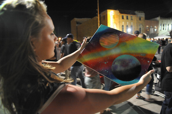 Ellie Houchin looks at a painting she purchased, Saturday, April 23, 2016, during Norman Music Festival 9. (Kyle Phillips / The Transcript)