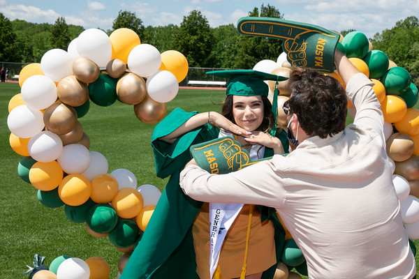 Graduates attend the Patriot Procession with friends and family for photo opportunities at the soccer stadium.  Photo by:  Ron Aira/Creative Services/George Mason University