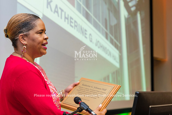 George Mason University Foundation President Trishana Bowden reads a plaque during a dedication ceremony renaming Bull Run Hall on George Mason's Science and Technology Campus to Katherine G. Johnson Hall in honor of the NASA mathematician. Photo by Lathan Goumas/Strategic Communications