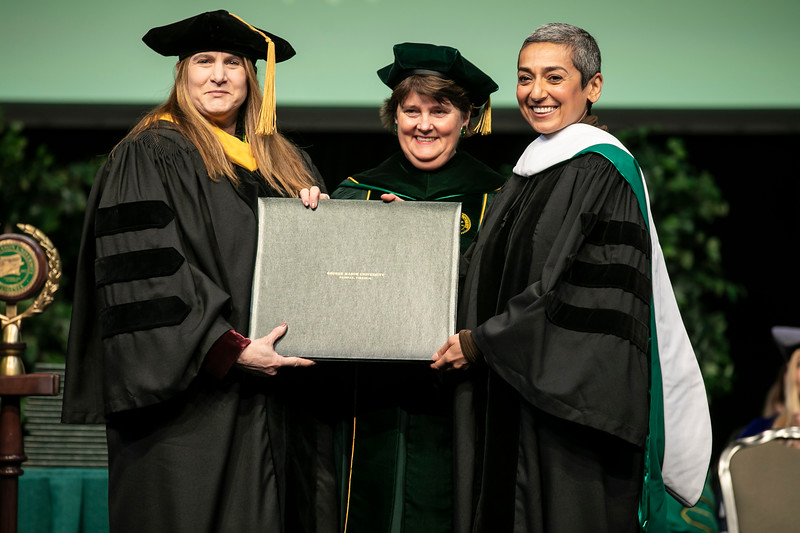 Zainab Salbi, right, receives an Honorary Degree from Interim President Anne Holton, middle, and Board of Visitor member Lisa Zuccari, left, during Winter Graduation 2019.  Photo by:  Ron Aira/Creative Services/George Mason University