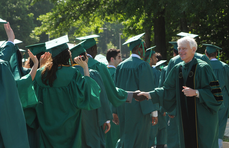 President Merten greets graduates as they process into the Patriot Center. Photo by Evan Cantwell