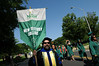 Associate Professor Tom Wood carries the New Century College banner during the Academic Procession. Photo by Evan Cantwell/Creative Services/George Mason University