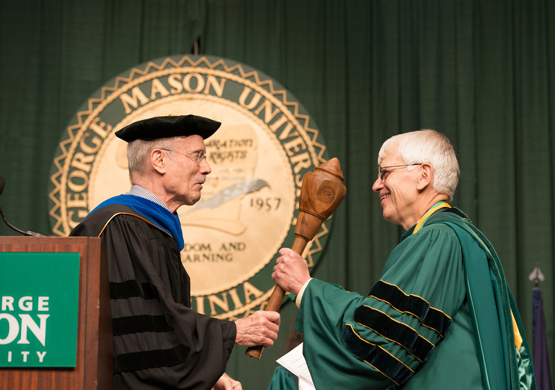 Ernst Volgenau presents the University Mace to Alan Merten at Commencement 2012. Photo by Alexis Glenn/Creative Services/George Mason University