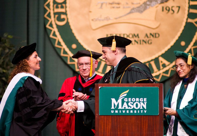President Ángel Cabrera shakes hands with the keynote speaker alumna Anousheh Ansari during the 2012 Winter Convocation. Photo by Craig Bisacre/George Mason University