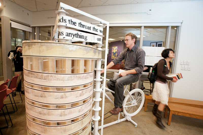 "Artist Matt Pinney rides his ""Bicycle Powered Movie Machine"" which is part of a collaboration with writer Brian Fitzpatrick, at the 2011 Fall for the Book series before the Call and Response Gallery Panel at Gallery 123, Fairfax Campus."