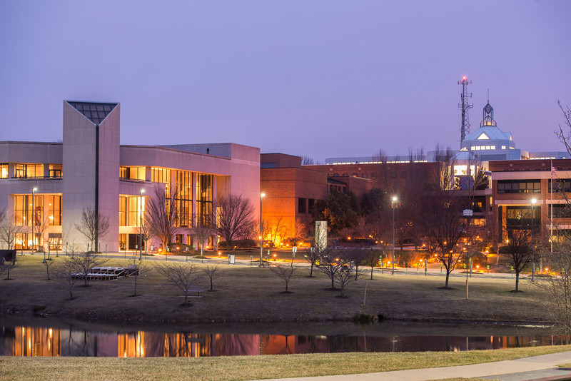 The Center for Fine Arts and the Johnson Center are seen near the Mason Pond at night. Photo by Alexis Glenn/Creative Services/George Mason University