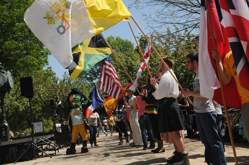 The Patriot poses with students from around the globe carry flags in the International Week flag parade. Photo by Evan Cantwell/Creative Services/George Mason University