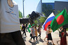 The George Mason statue frames students from around the globe carrying flags in the International Week flag parade. Photo by Evan Cantwell/Creative Services/George Mason University