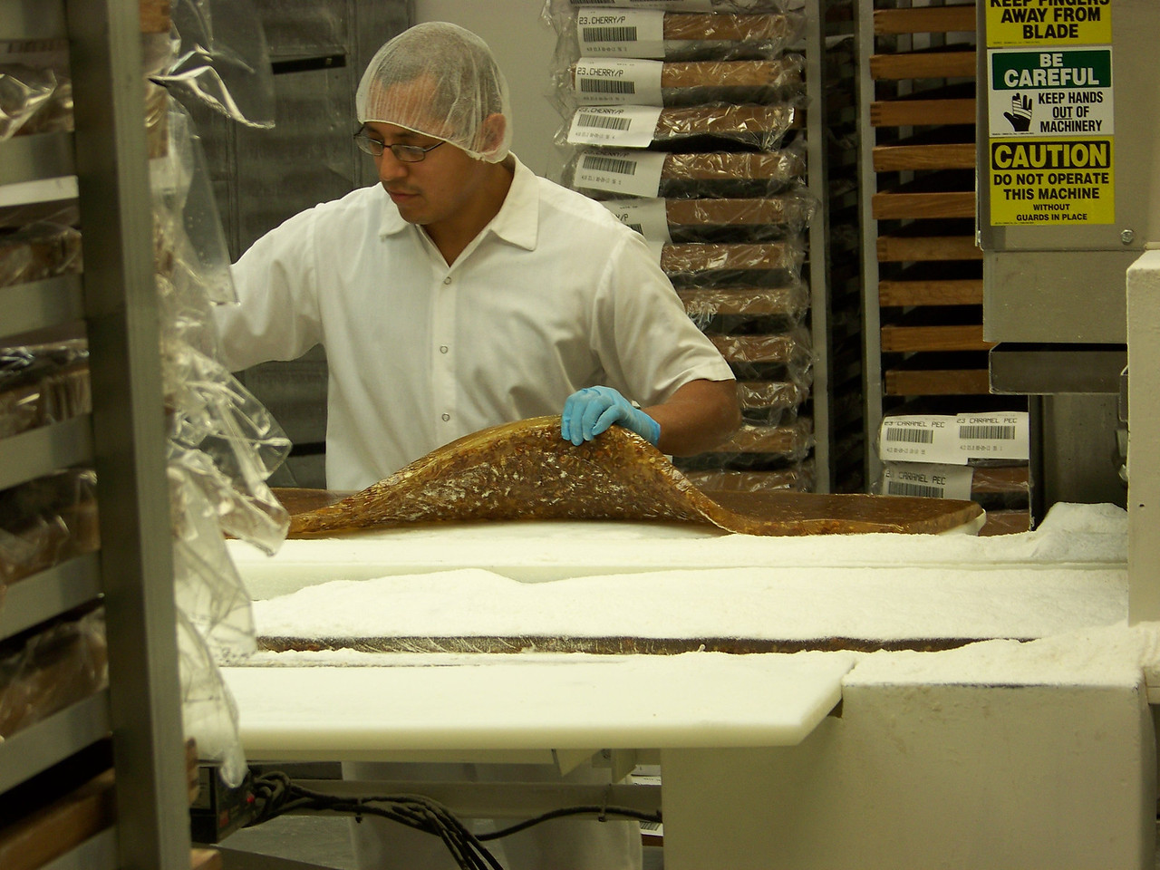 The cooled sheet of fruit and nuts is removed from its tray (seen here) and is then fed through a machine which both cuts the sheet into bite-sized rectangles, and covers the pieces with powdered sugar.<br /> [Cashmere, WA - Aplets & Cotlets factory tour]