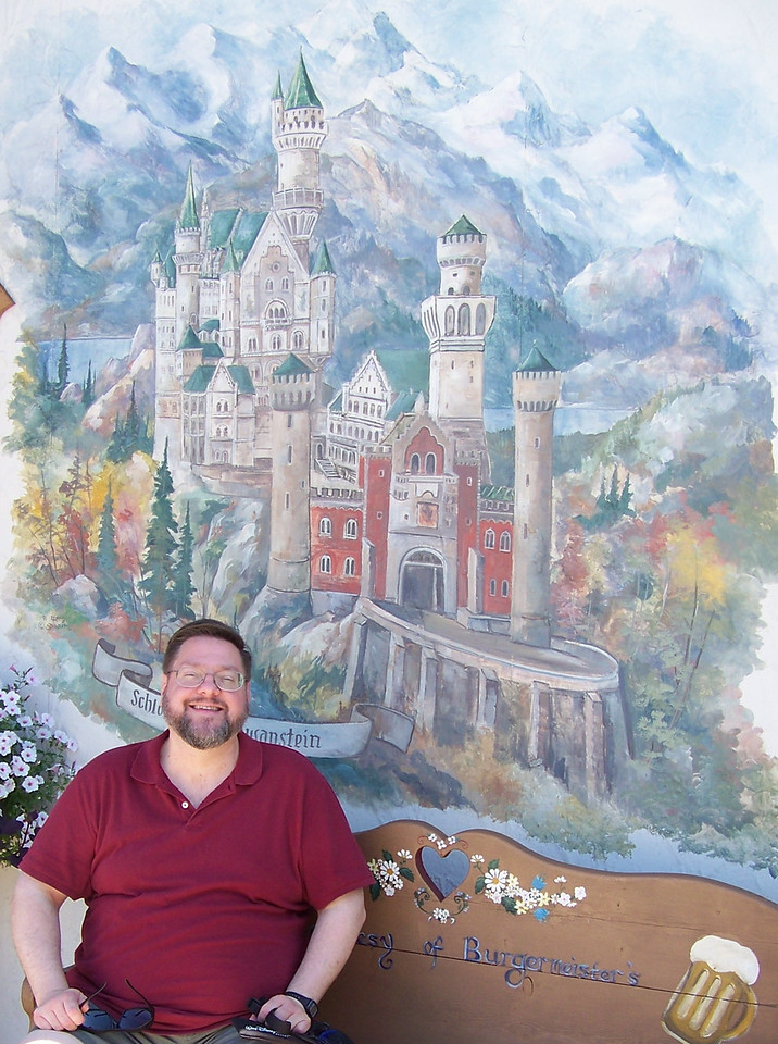 Outside the restaurant, Jon poses with a mural featuring Neuschwanstein, the famous castle built by King Ludwig of Bavaria.  It was one of the inspirations for Disneyland's castle!<br /> [Leavenworth, WA]