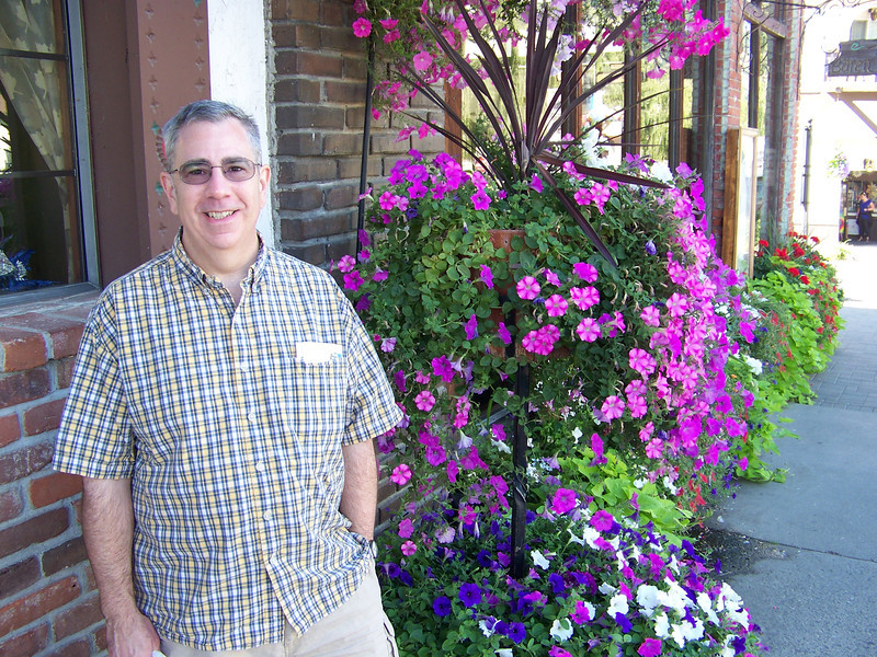 "The next morning, we did some more shopping along Front Street, where Dave posed with these flowers.  It's not pictured here, but one of my favorites was the <b><a target=""_new"" href=""http://www.cheesemongersshop.com/"">Cheesemonger's Shop</a></b>.  I bought two different varieties of cheese (chipotle cheddar and smoked gouda), and also some frozen sausages there. [Leavenworth, WA]"
