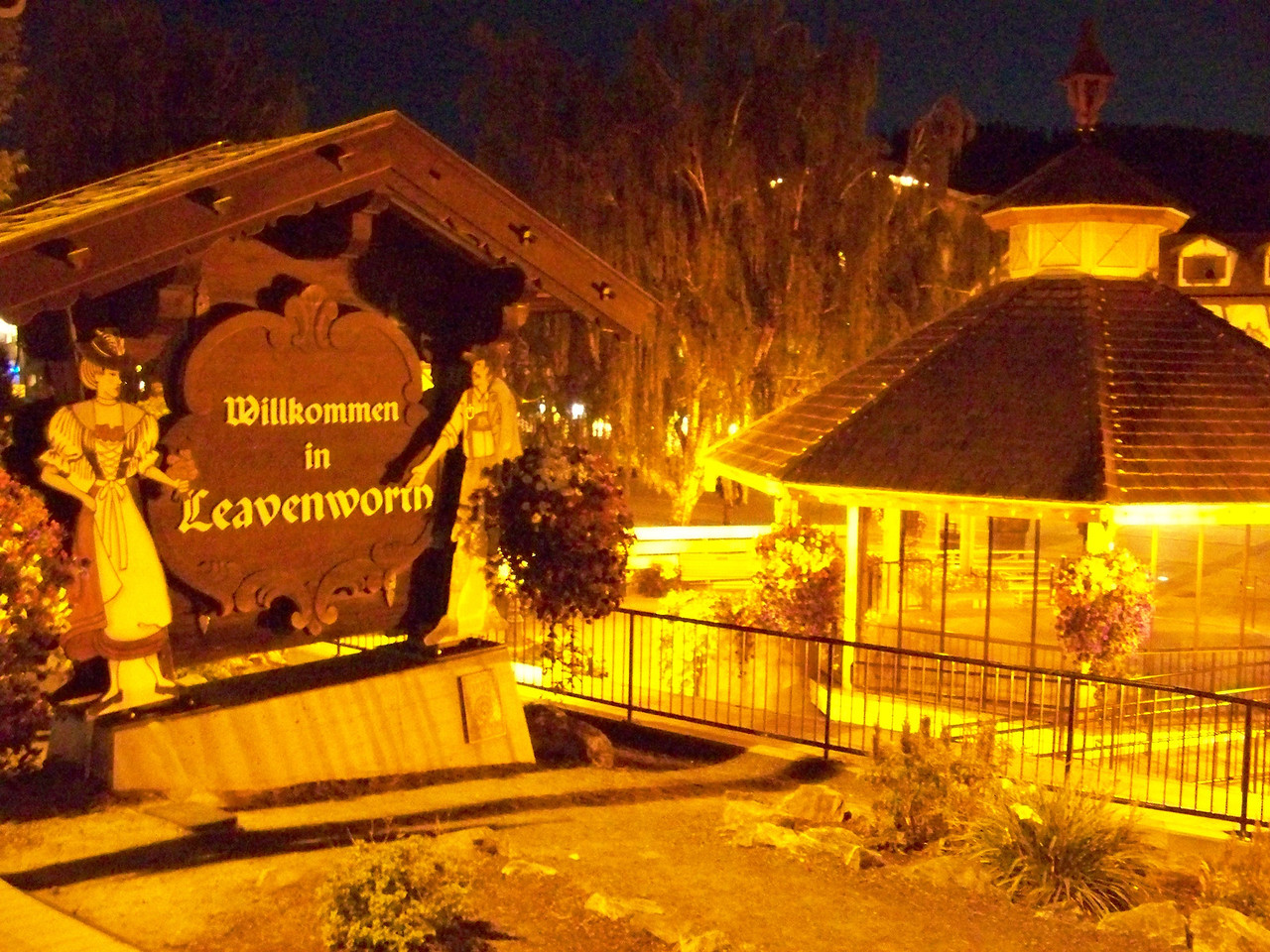 After the show, we walked from our hotel back to the central part of town.  Everything was closed, so we didn't stay long.  The welcome sign here can be seen from Highway 2.  On the right is the little park's gazebo again.<br /> [Leavenworth, WA]