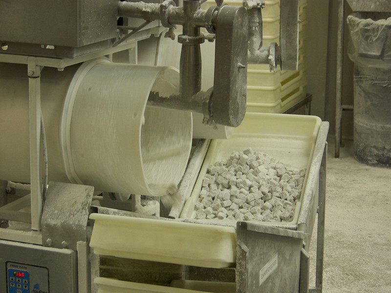 The finished candy pieces come sailing out of the spinning white cylinder on this end of the machine, and are collected into a bin.<br /> [Cashmere, WA - Aplets & Cotlets factory tour]