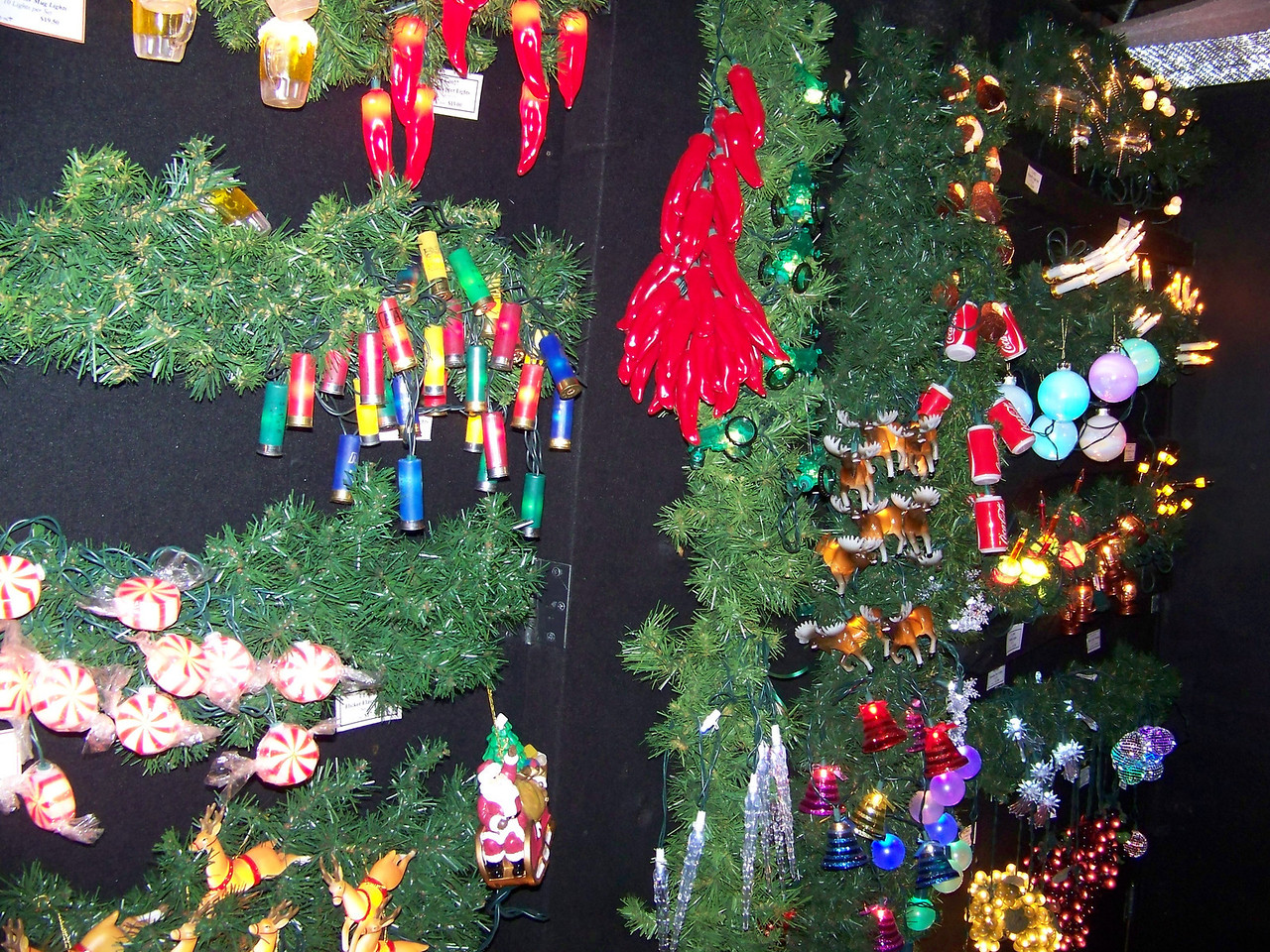 """Part of a display of Christmas lights at the Kris Kringl shop.  Clockwise from the lower left, you can choose from Santa and his reindeer, peppermint candies, shotgun shells (?!), beer steins, two different kinds of peppers, tractors, owls, dragonflies, candles, Coca-Cola cans, moose, snowflakes, disco mirror balls, bunches of grapes, bells, and icicles, among many others. [Leavenworth, WA - December 2013 - <b><a target=""""_new"""" href=""""http://youtu.be/NqCqDCOY_tc"""">Watch my video here</a></b>]"""
