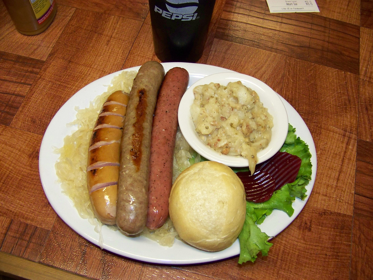 """My lunch at the Soup Cellar was great!  After a cup of broccoli & cheese soup, I had the sausage sampler plate--three different types of sausage served on a bed of sauerkraut, with German potato salad, and a roll.  Yum! [Leavenworth, WA - December 2013 - <b><a target=""""_new"""" href=""""http://youtu.be/NqCqDCOY_tc"""">Watch my video here</a></b>]"""