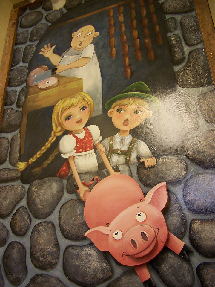 """This mural was above the stairs that go down to the Soup Cellar.  The pig seems happy enough, but based on the kids' expressions, I'm still not certain if they're helping him escape or dragging him to his butchery doom!  :-) [Leavenworth, WA - December 2013 - <b><a target=""""_new"""" href=""""http://youtu.be/NqCqDCOY_tc"""">Watch my video here</a></b>]"""