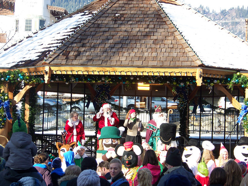 """After their carriage entry, Santa, Mrs. Claus, and Father Christmas kicked off the day's festivities.  In front of them are a number of costumed characters who roamed around and posed for pictures.  A variety of musical acts--from oompah bands to school choirs--performed on this gazebo throughout the day. [Leavenworth, WA - December 2013 - <b><a target=""""_new"""" href=""""http://youtu.be/NqCqDCOY_tc"""">Watch my video here</a></b>]"""