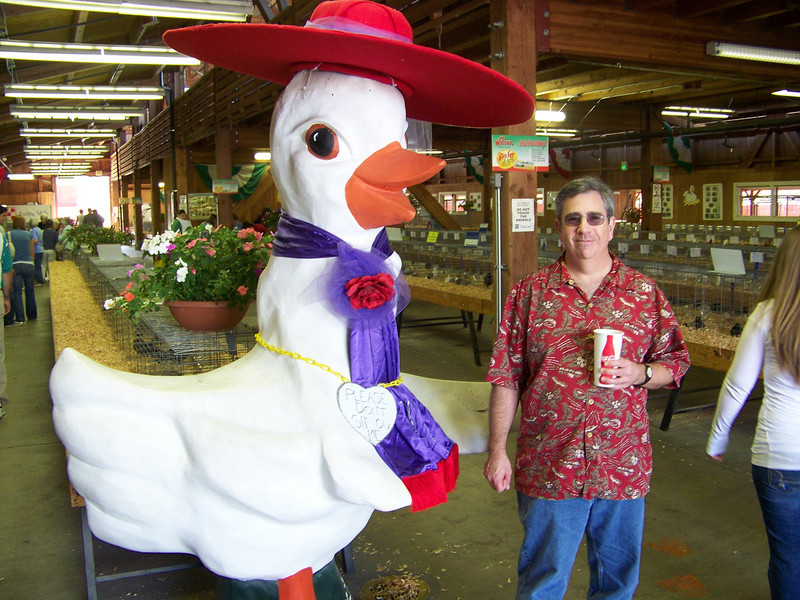 Dave and a giant chicken.  Which is scarier--its size, or the way it's dressed up as a Red Hat Lady?  :-)<br /> [Puyallup, WA Fair 2009]