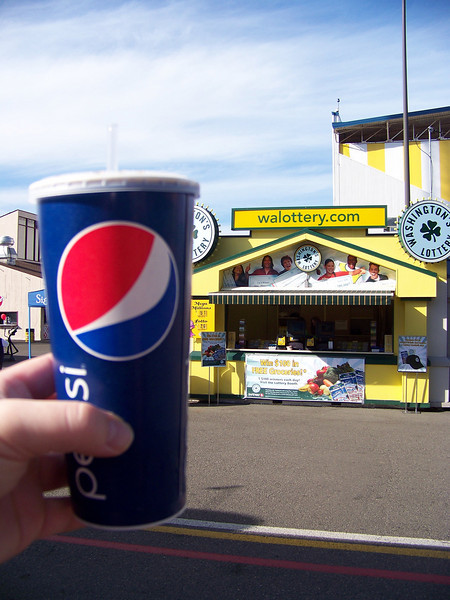 This was the low point of my Fair experience.  On the right is the Washington Lottery booth where I lost $22.00 on scratch tickets.  And on the left is the pop I bought at a food stand which cost me $4.00 (plus tax).  That's way worse than Disneyland!!!  Other stands had drinks for less, but I managed to find the most-expensive one at the entire fair.  I bought the drink with a food order, and never even considerd the price of the drink itself until I was wondering why the total was so high.  You better believe that I savored every drop, and then refilled the cup from water fountains several times to get every stinkin' penny's worth out of it!<br /> [Puyallup, WA Fair 2009]