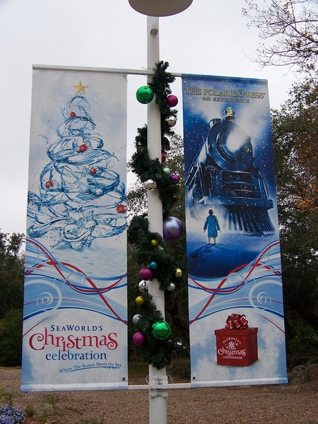 Light poles around the tree were decorated with banners advertising the various shows and attractions in the park.  I like the Christmas tree on the left that looks like it's made of water splashes.  Later that afternoon, I saw the Polar Express film being advertised at right, but I wasn't impressed.  It was a 15-minute condensed version of the feature film with some minimal in-theater effects.  Meh.<br /> [SeaWorld San Antonio]