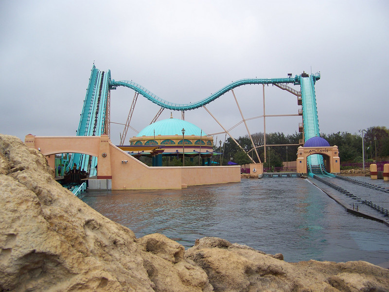 This ride is called Journey to Atlantis.  Riders board a boat in the station on the left side.  On the top of the track, there's a turntable in either corner.  The boat is rotated in the left corner of the track so that the riders will go through the dip in the middle section backwards.  Another rotation happens in the right corner, and the boats face forward to plunge down the big hill.<br /> [SeaWorld San Antonio]