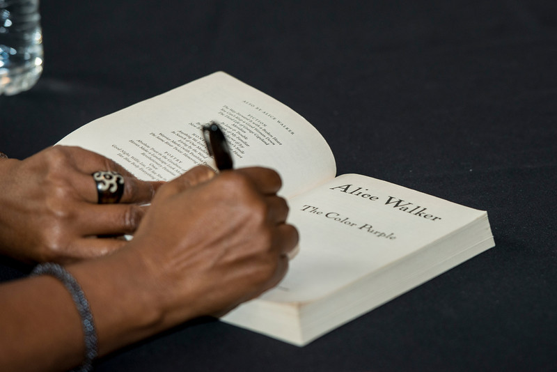 """Author Alice Walker signs a copy of her book """"The Color Purple"""" during a Fall for the Book event at the Center for the Arts at Fairfax campus. Photo by Alexis Glenn/Creative Services/George Mason University"""