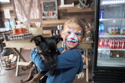 Noah Holly hugs on her dog Oochee after getting her face painted.