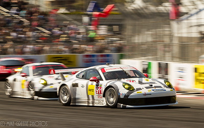 The two Porsche North America team Porsche 911 RSR cars in turn 10, during the Tequila Patron Sports Car Showcase race on Saturday, April 12, 2014
