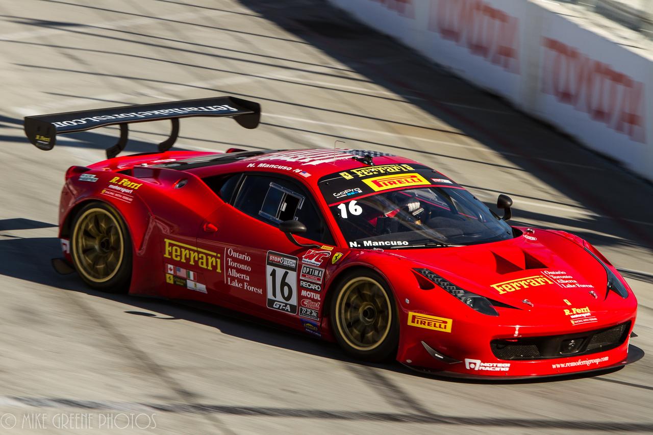 Ferrari 458 GTLM car powers through Turn 1, as part of the Tudor United Sportscar Championship series