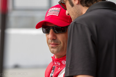 Tony Kanaan consulting with Dario Franchitti in the pits.