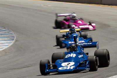Elf Power !   The ex-Jody Scheckter1974 Tyrrell 007 owned by Nicholas Colyvas leads the train down the Corkscrew in Saturday's Group 5 qualifying race (Photographer:  Mike Greene)