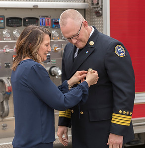 As part of the swearing in ceremony for Fire Chief David Pennington, Amy Pennington removes the old badge from her husband's uniform.