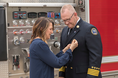 Immediately after taking his oath of office, Chief David Pennington's wife, Amy, pins a new badge to his uniform.