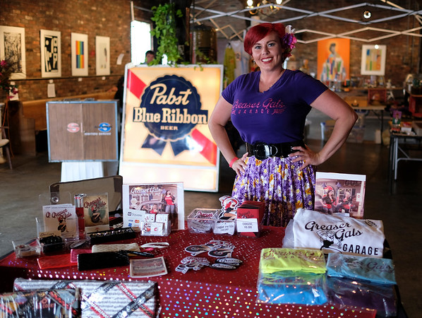 "Kimberly Petree aka Pearle De Lux stands by her table for the Greaser Gals Garage where she sells t-shirts and also her hand made jewelry and hair bows. ""It's originally a bunch of us girls that are learning how to work on our own cars. I've got a 1953 Chevy Bel Air I work on, and my business partner has a 69 Chevelle.  I have some other friends that have newer Jeeps and Camaros, and we just kind of have our own thing… It's almost like a social club, and we like to go to the different events and travel around to look at cars."""