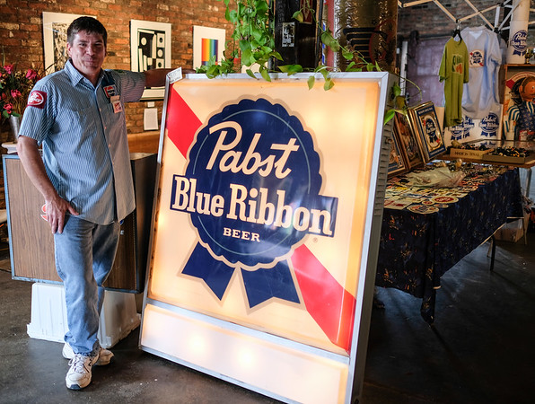 """Derrin Pickett of Evansville, Indiana poses beside his large Pabst Blue Ribbon Beer sign next to his display tables at the Beatersville Car and Bike Show.  Pickett says that he sets up about four or five times a year at different car shows with his beer and car memorabilia. """"I kinda dig on it. I used to be all toys, like the hot-wheels, action figures and stuff.  I did this show back in 09' and the guy next to me was selling all of this cool beer stuff. I see that stuff all the time at garage sales and good will, and I just didn't know there was a market for it.  But it's this young hipster crowd."""""""
