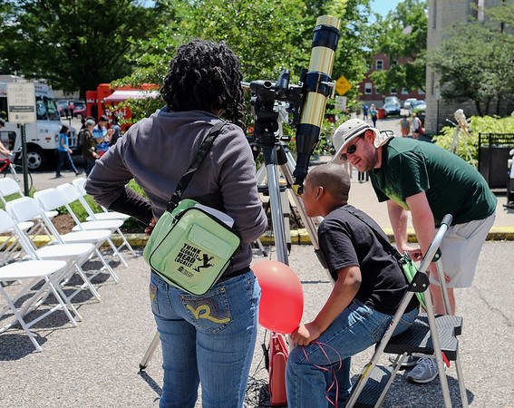 Scott Lookabill (right) shows festival goers how they can look directly at the sun through a telescope with the help of a special safety filter.